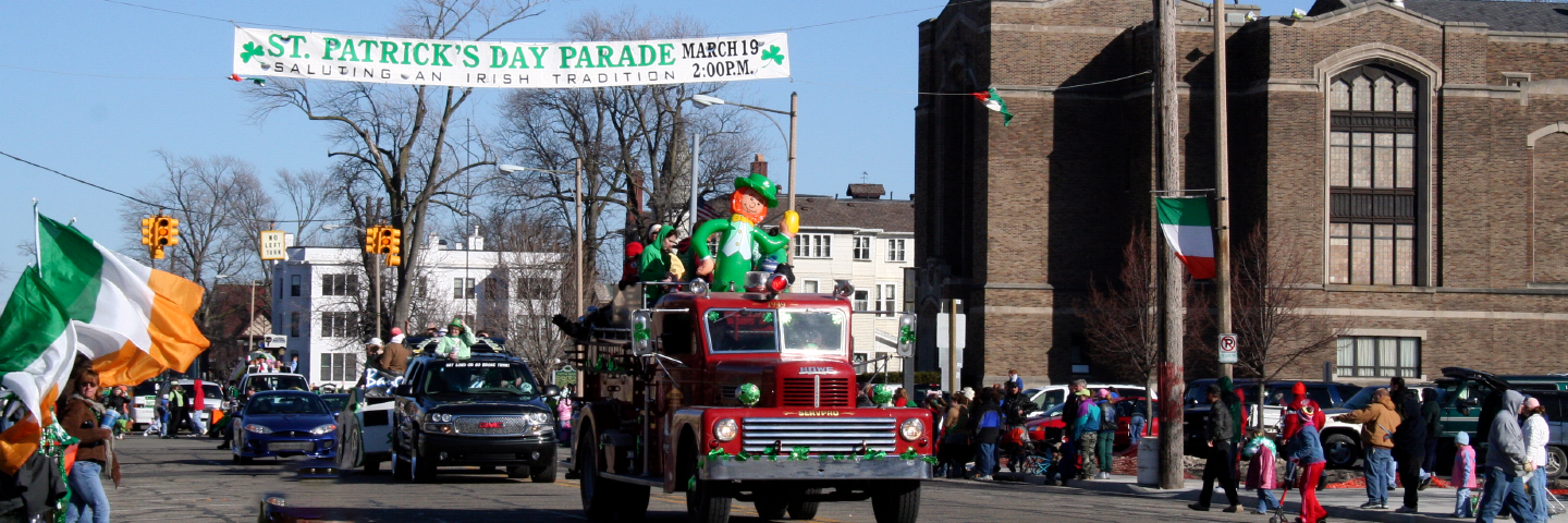 Historic firetruck and other cars drive in Bay City Michigan St Patricks Day Parade