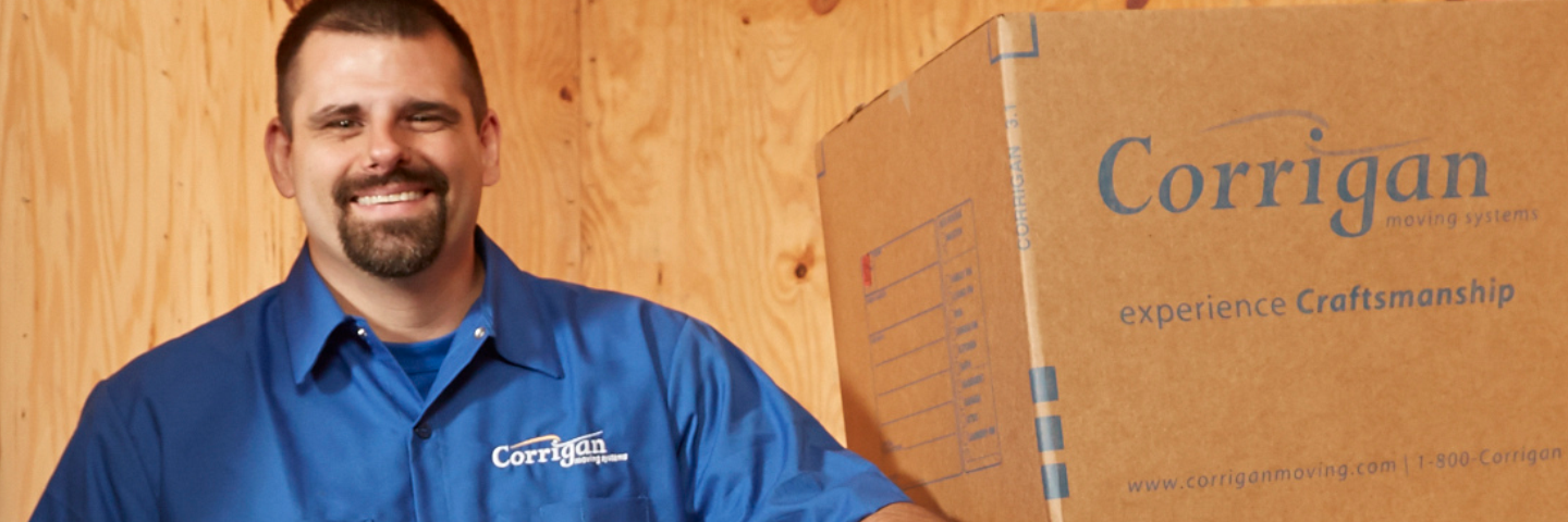 mover in blue uniform standing next to stack of boxes with Corrigan logo