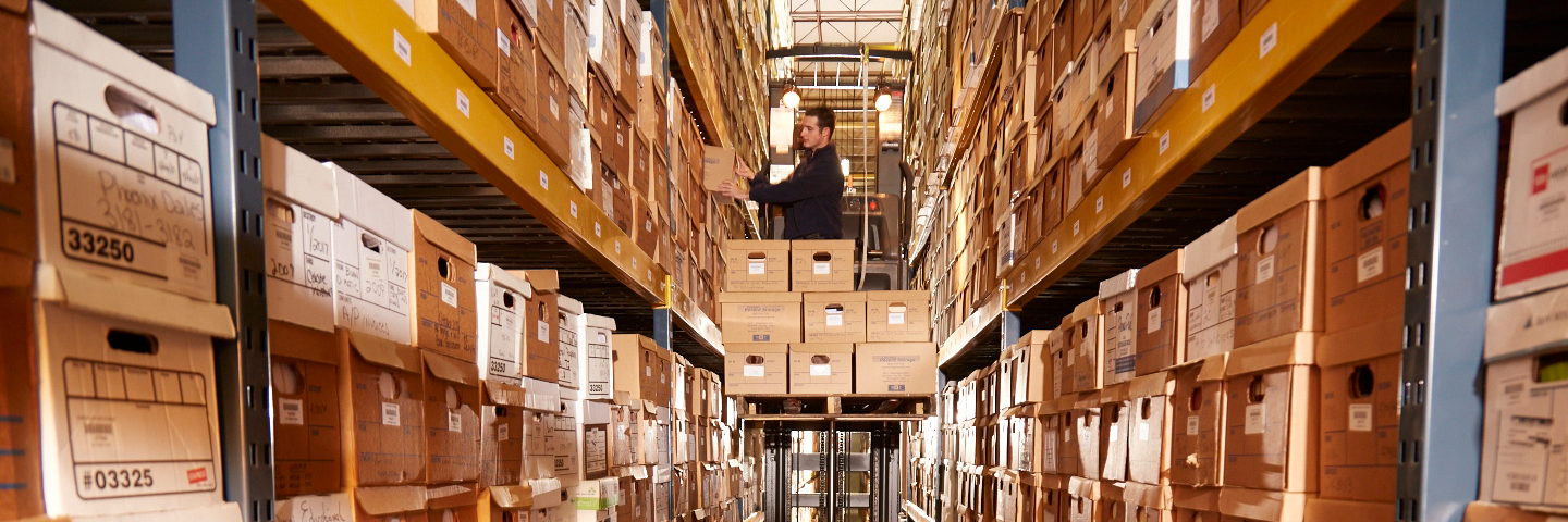 man standing on order picker placing a record storage box onto racking with hundreds of other record storage boxes