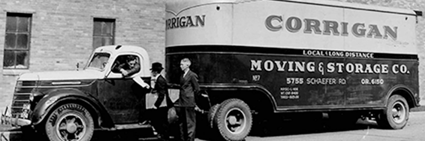 historic image of tractor trailer truck. a man stands next to the cab of the truck