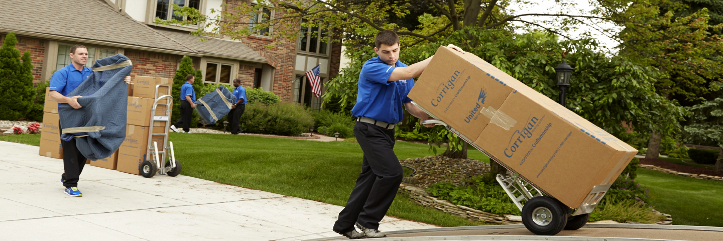 movers carrying boxes and wrapped furniture to moving truck