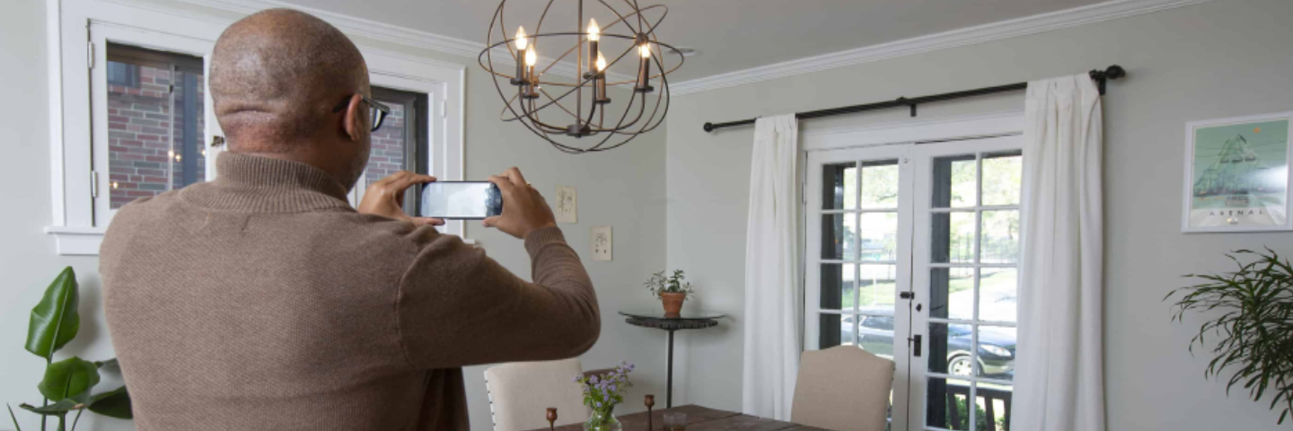 man holding smart phone having a virtual home survey with moving representative